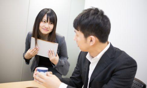 男性社員を笑顔で見つめる女性社員