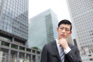 オフィス街で考える若い男性