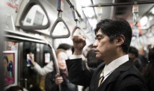 電車に乗る疲れたサラリーマン
