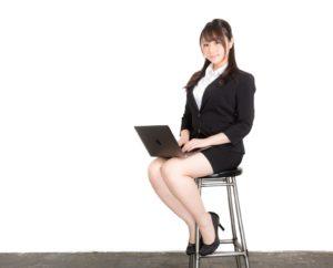 パソコンを持って椅子に座る女性